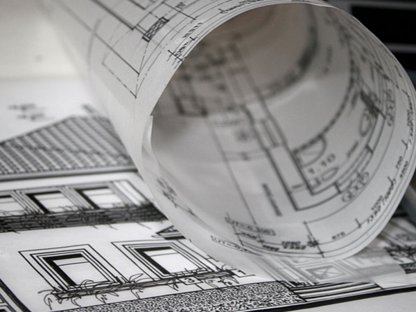 image shows architect's drawing with roll of tracing paper in article: planning consultant vs architect